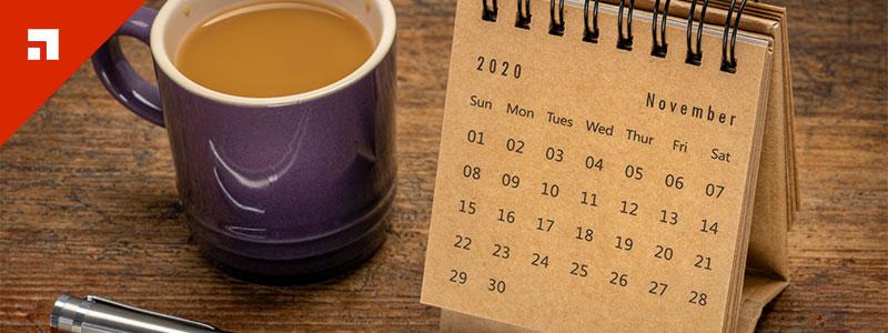 nov 2020 calendar with coffee mug and pen on wooden desk